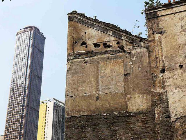 朽ちかけた建物とモダンなビル